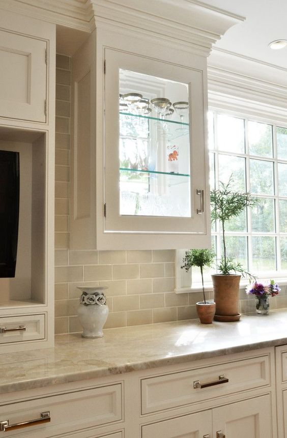 traditional cabinetry with beige subway tiles and matching quartz counters