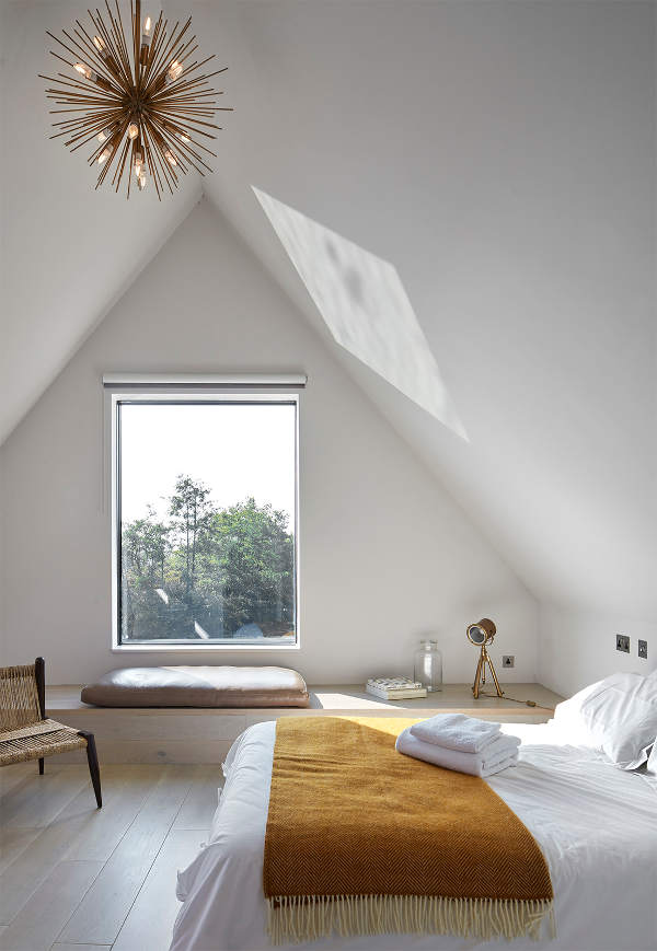 A guest bedroom with a cool platform instead of a usual window sill, it's good for storage
