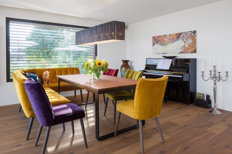 The dining area is colorful and inviting, with upholstered chairs of jewel colors