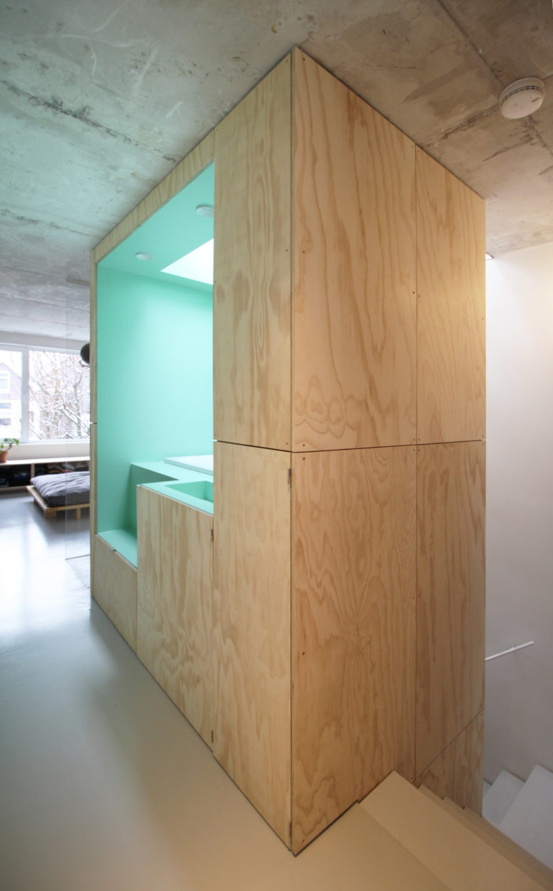 A bathroom combo is located inside a wooden cube