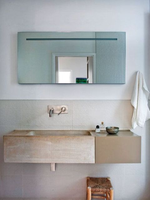 The bathroom is modern and functional like the kitchen but a stone sink and a jute chair bring that light Moroccan flavor