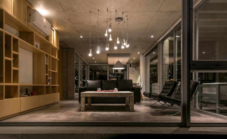 The living room features black leather furniture, a large light wood storage unit and amazing pendant lights