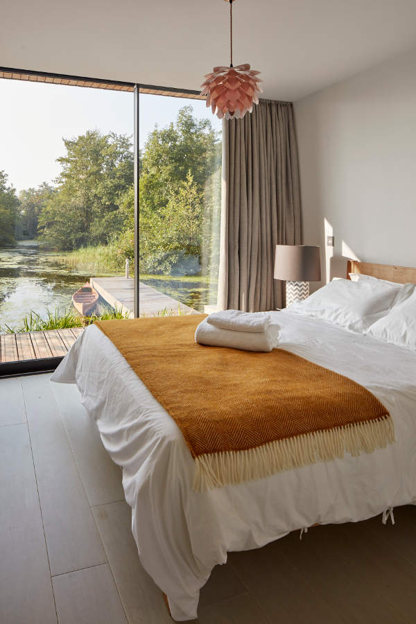 The master bedroom shows beautiful views of the lake and a cool cozy bed, nothing else needed