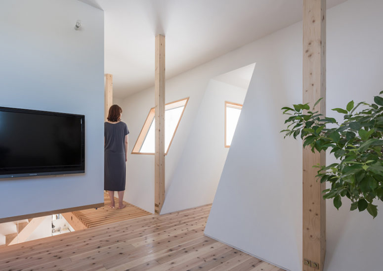 White walls are softened with light-colored wooden floors and window framing