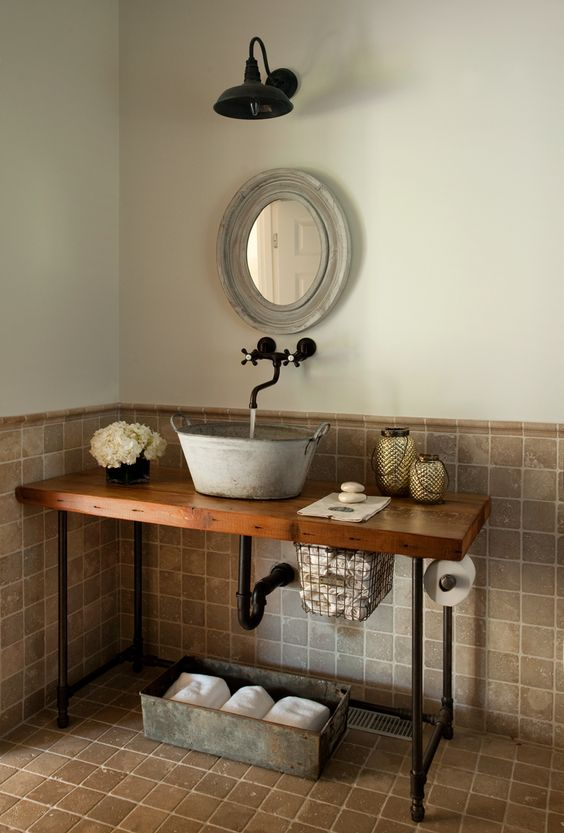 a galvanized bathroom sink on a wooden countertop with black pipe legs