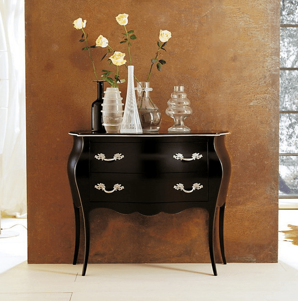 dark wood dresser with shining metal handles and lots of vases on display