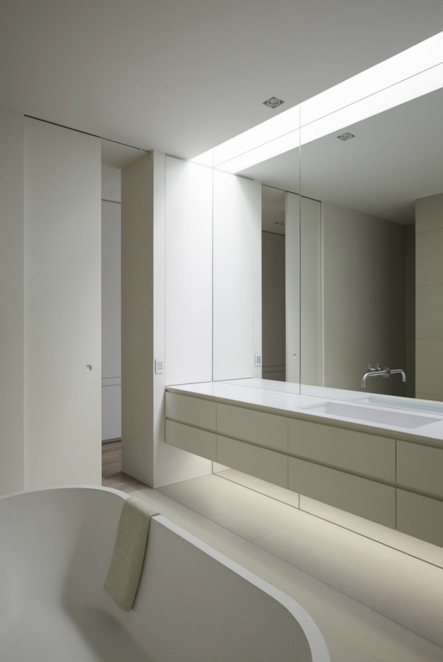 minimalist bathroom in white and a mirror wall with a vanity