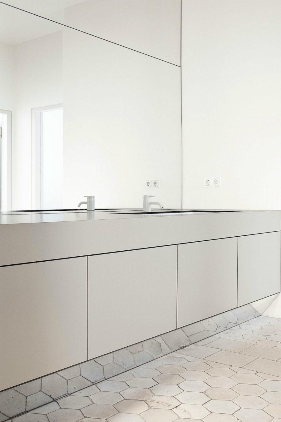 minimalist bathroom with hexagon tiles, sleek cabinets and a mirror wall