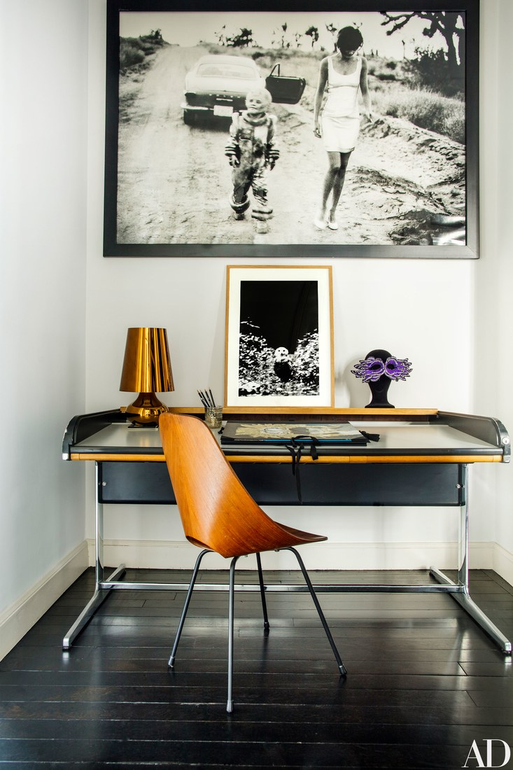 Home office nook with a black desk and a bent wood chair, there are bold orange-ocher details that make it cozier