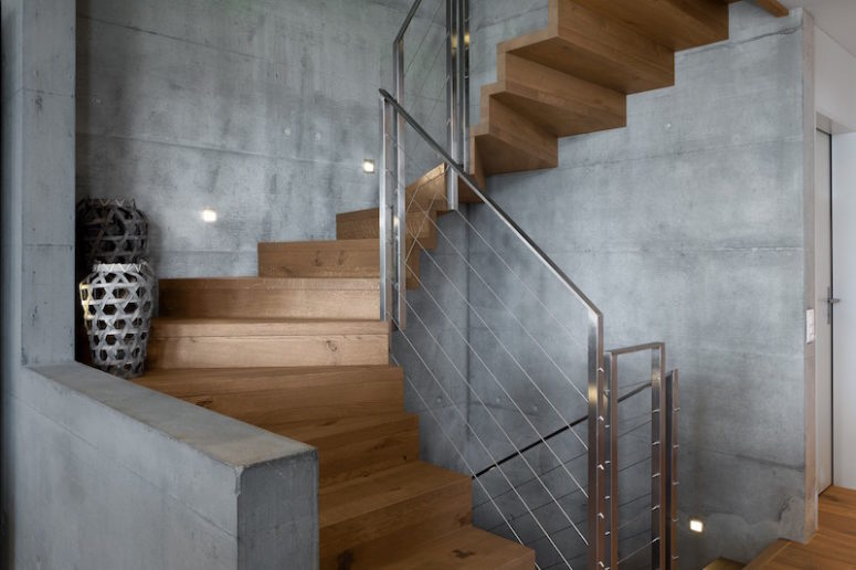 The spiral staircase has a very graceful and elegant design, featuring a combination of wood and concrete