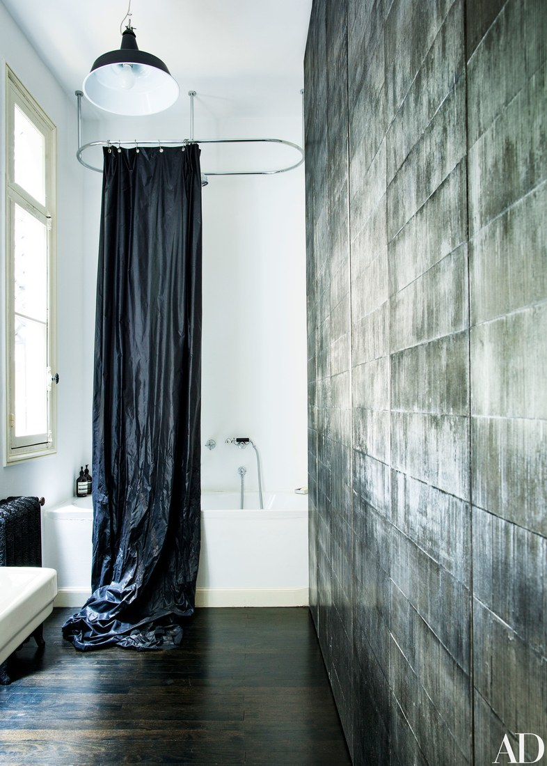 The bathroom features a unique wall and a black curtain for a white bathtub, looks very fashionable