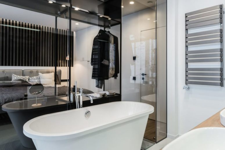 The bathroom is behind a glass partition, which is an interestig solution