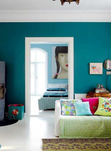 a teal statement wall and lime green accessories are a great combo for a vivacious living room