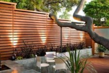 11 modern backyard with a horizontal wood fence and concrete planters along it