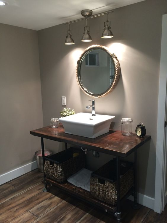 dark stained wooden and metal pipe vanity with baskets instead of drawers