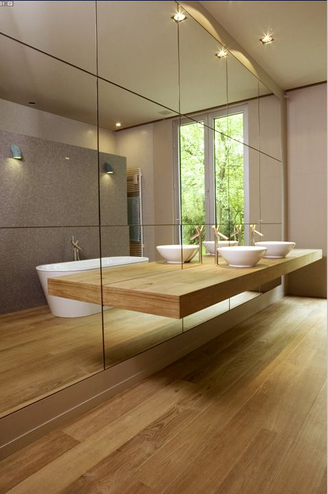 minimalist bathroom with light-colored wood and a mirror wall and a thin counter not to spoil the look