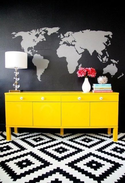 black and grey world map wall mural looks contrasting with a neon yellow sideboard