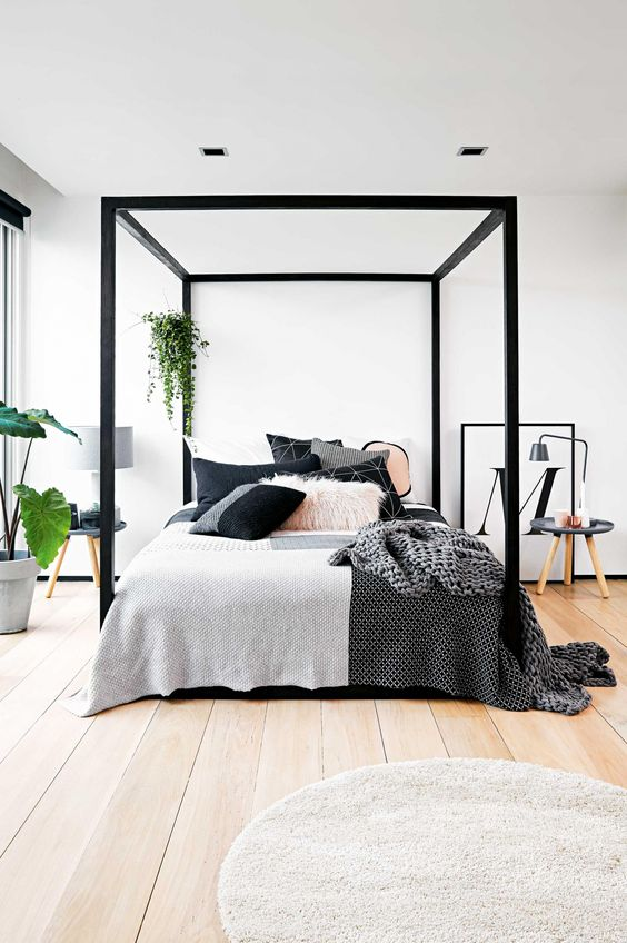 chic modern bedroom with a black frame bed and lots of greenery