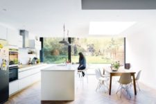 13 light-filled kitchen in white with a large kitchen island and dinign area with mid-century modern furniture