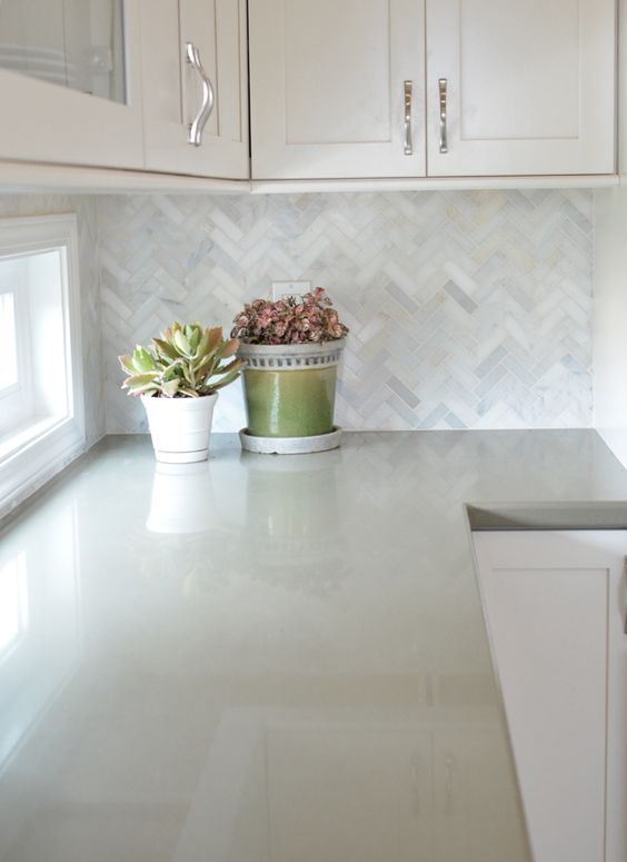 with marble herringbone backsplash and sage green quartz countertops