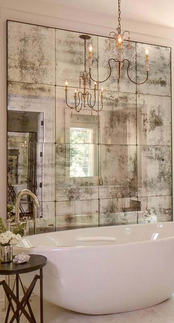 antique mirrors add a glamorous vintage vibe, and a chandelier highlights it