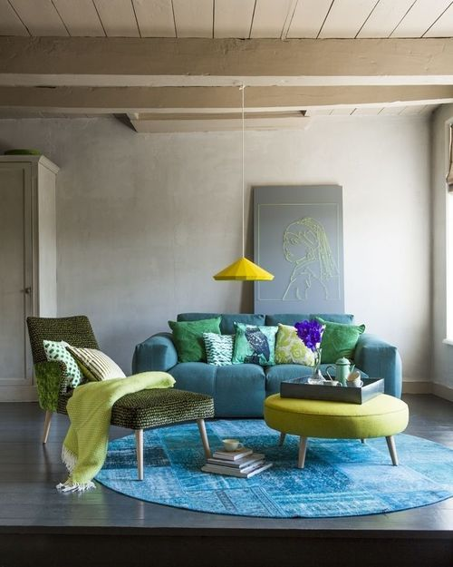 blue, emerald and lime green living room with a round carpet and a round coffee table