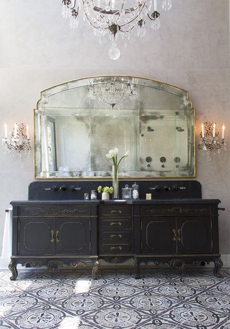 refined black vanity with gold contours and a large mirror