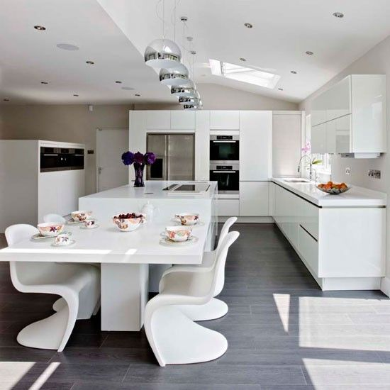 Ultra Modern White Kitchen And A Corresponding Dining Space With Sculptrual Chairs