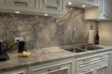 15 white cabinets and grey quartz counters and a backsplash for a stylish statement