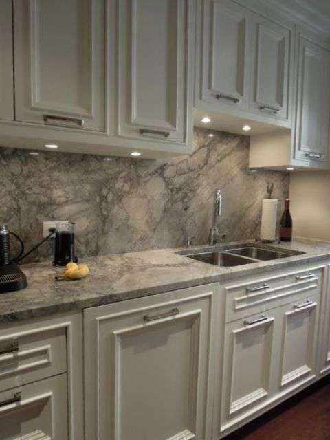 white cabinets and grey quartz counters and a backsplash for a stylish