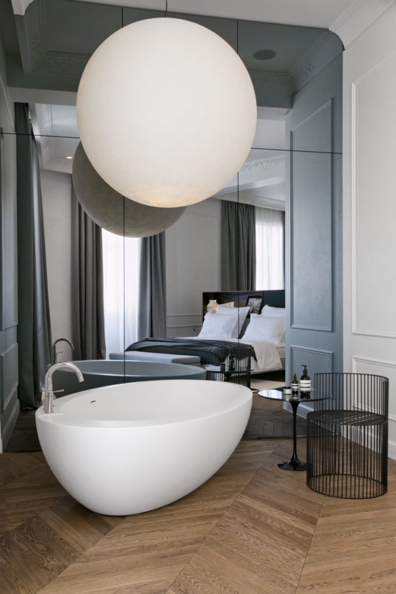 modern mirror wall, a free-standing bathtub and an oversized sphere lamp