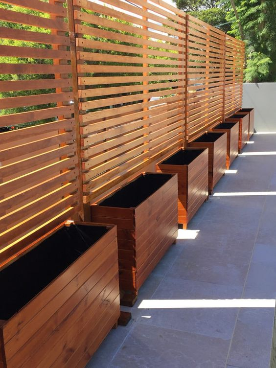 wooden privacy screens with planters to make your backyard cozier
