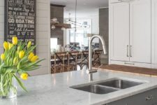 17 gray kitchen island topped with white quartz fitted with a stainless steel dual sink