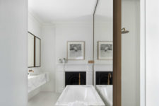 18 a marble bathtub in front of a mirror wall and mirrors on the opposite wall