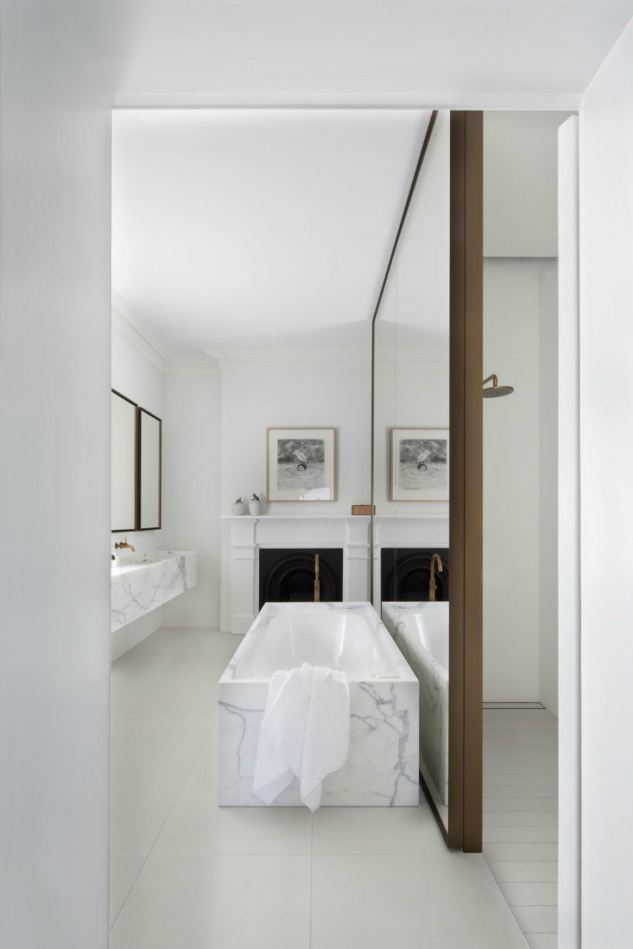 a marble bathtub in front of a mirror wall and mirrors on the opposite wall