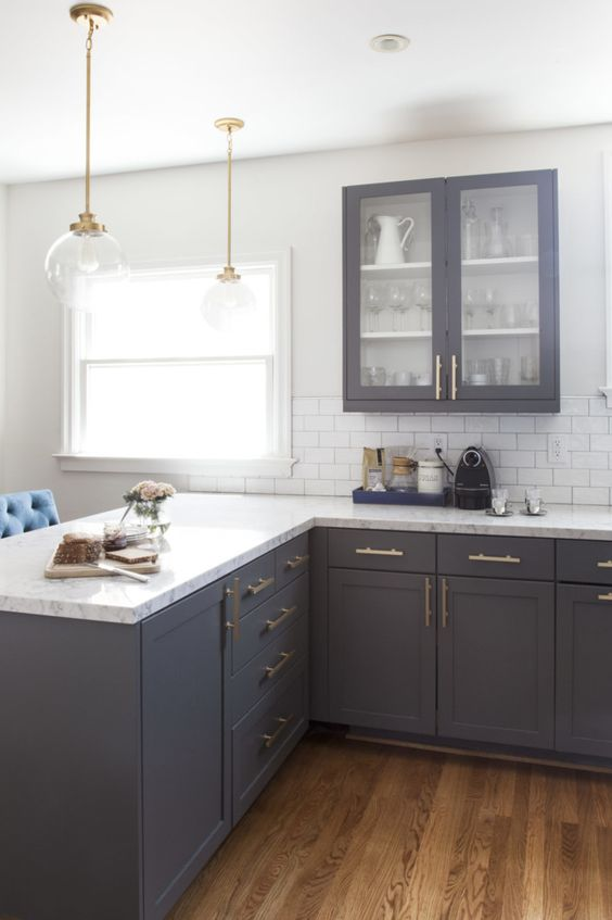 vintage dark grey cabinets with white quartz countertops and brass details