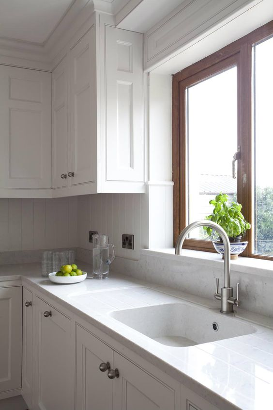 all-white kitchen with tiles and quartz counters