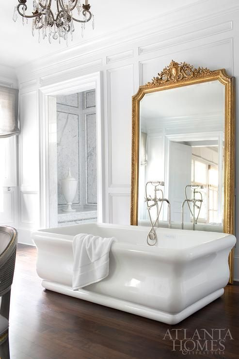 large mirror in a refined gilded frame is a great deoc ridea for a bathroom