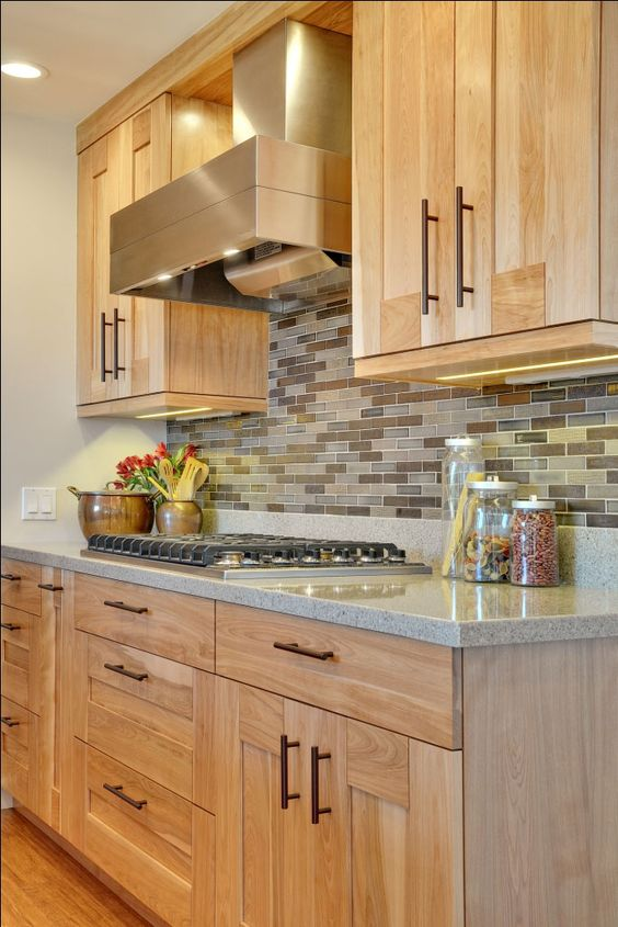 light-colored kitchen cabinets with a earth-tone backsplash and a grey quartz counter