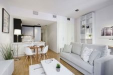 20 small space uniting a kitchen, a diner and a living room all decorated in modern style and off-whites