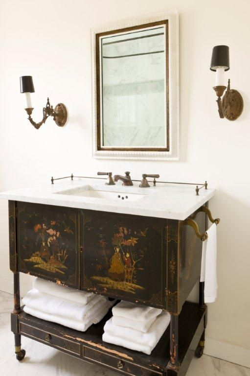 adorable vintage vanity with painted images, an open shelf and a marble counter