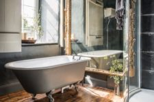 21 dark bathroom decor, a vintage free-standing bathtub and a large mirror in a refined gilded frame