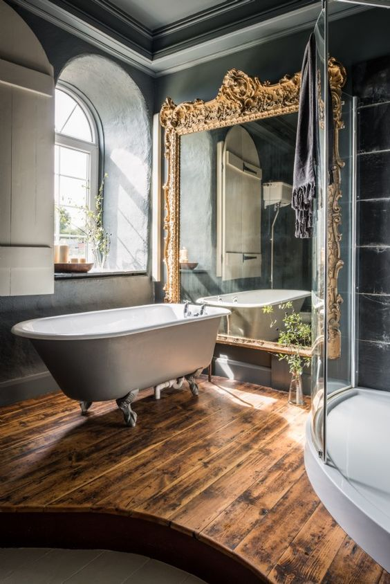dark bathroom decor, a vintage free-standing bathtub and a large mirror in a refined gilded frame