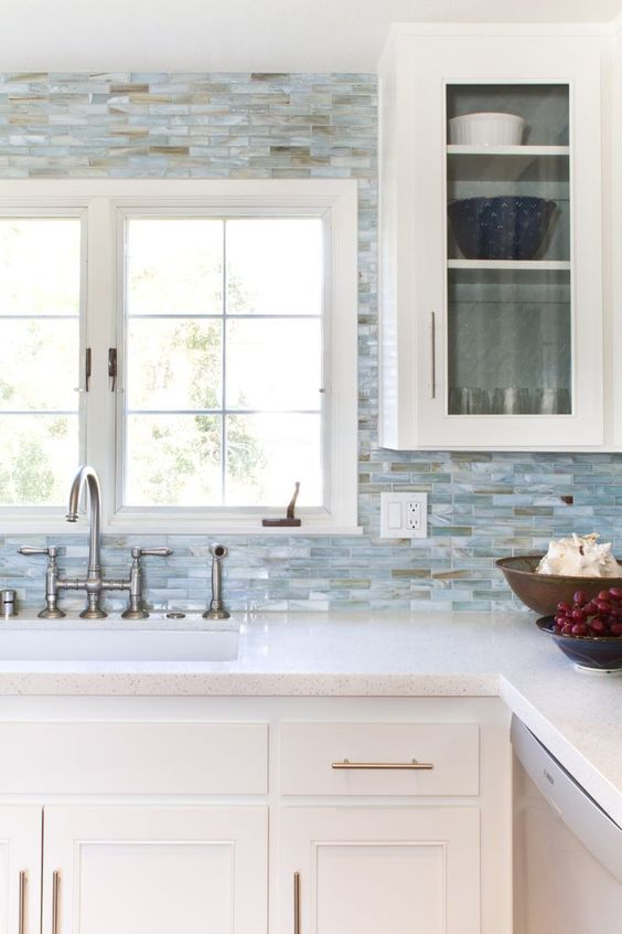 white cabinets, small blue tiles all over and white quartz countertops