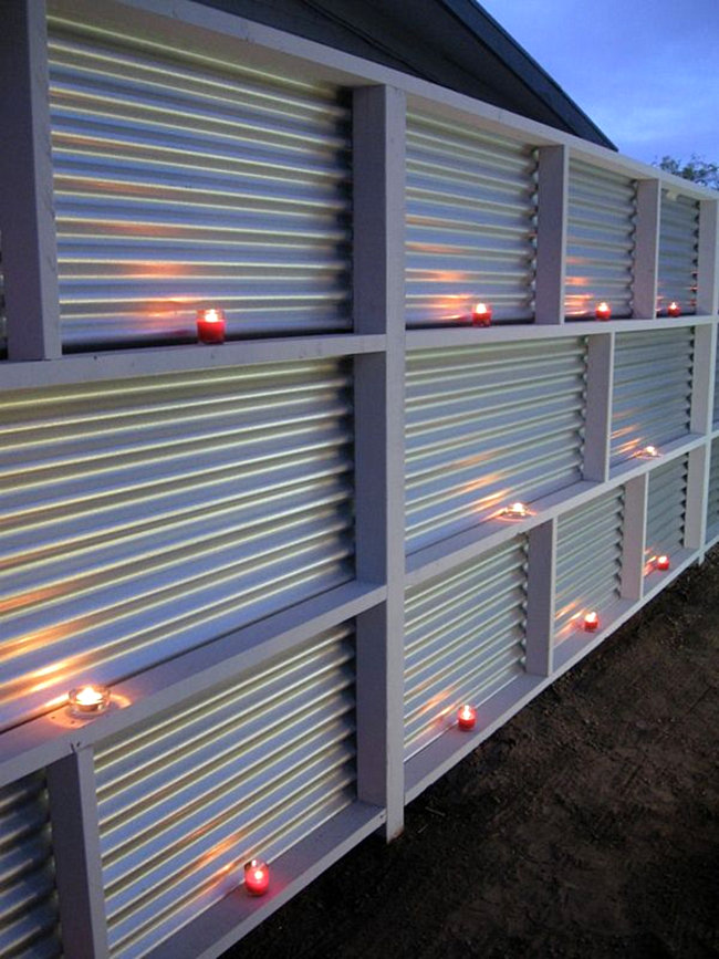 a corrugated metal fence can become realyl cool-looking if you place some candles there
