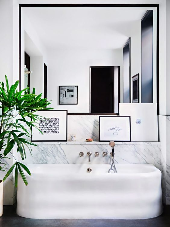chic modern marble bathroom with a free standing bathtub and a framed mirror