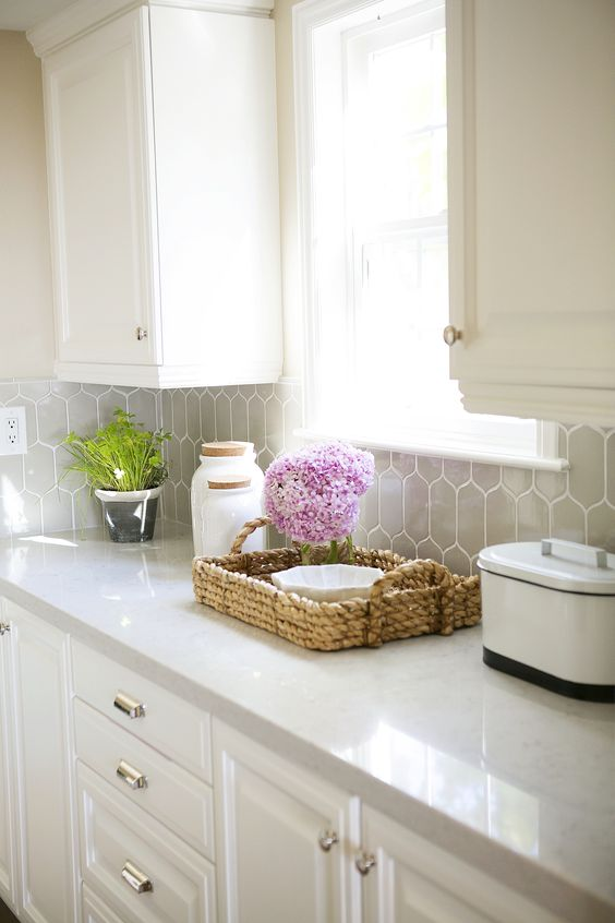 traditional white kitchen with grey hexagon tiles and and off-white quartz counters