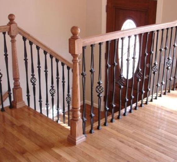 Chic Light Colored Wooden Staircase With Dark Wrought Metal Railing For A Contrast