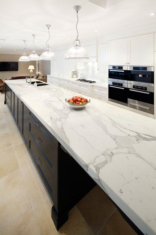 modern white kitchen cabinets and a black kitchen island with chic white quartz countertops