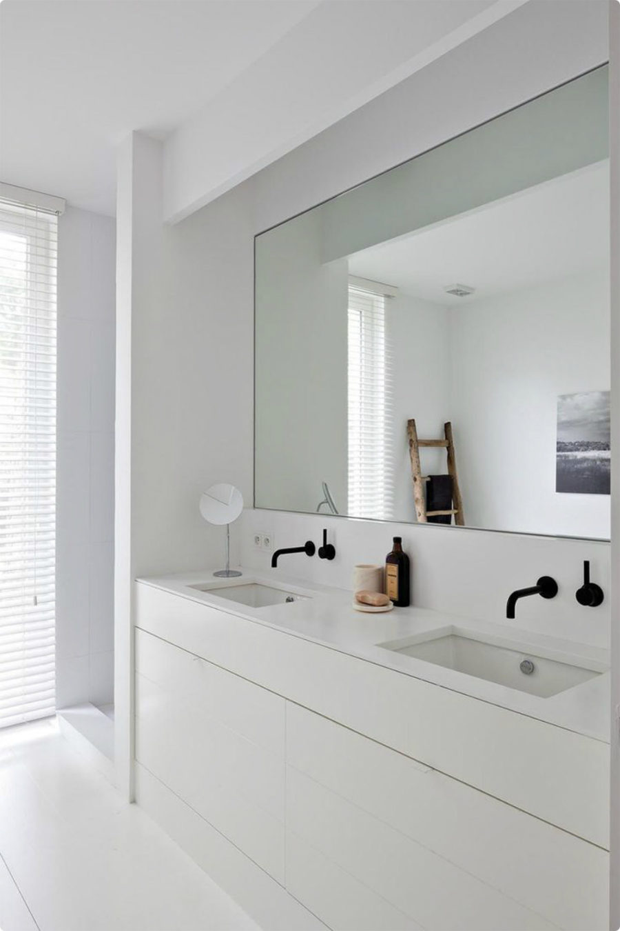 ultra minimalist white bathroom with a mirror niche to accentuate the sink area